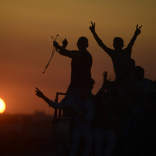 Silhouettes of protesters making V for victory signs and holding slingshots are seen against a setting sun
