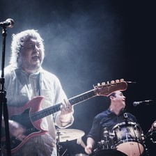 Concert photo of Richard Dawson playing guitar on stage with drummer in background
