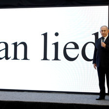 Netanyahu stands on stage with Iran lied in giant letters projected on a screen behind him