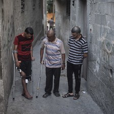 Three men stand in an alley, two of them using crutches.