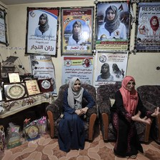 Two women sit on chairs in room with walls covered with posters of Razan al-Najjar in medic's uniform