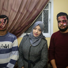 "Alaa Abu Mustafa stands between two of her ""zombies."" One her right, a man has his face apaprently split open, with bones protruding. On her left, a man's eye is made out to be dangling down his cheek."