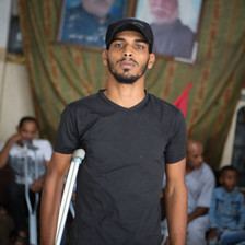 Young man using crutch is seen from waist up