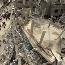 Birds-eye-view of people standing next to the rubble of a mosque