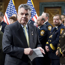 Peter King, a member of Congress for New York, stands beside US flags and soldiers in uniform.