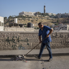 A man pushes trash with a broom along a street