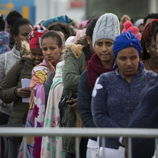 Women wearing winter clothing stand in a queue