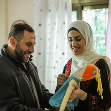 A smiling Imad al-Din al-Saftawi looks at a plush doll held by a smiling young woman