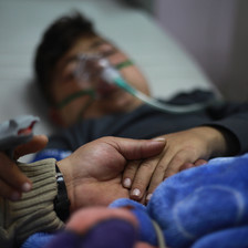 Young patient on a hospital bed, with a mask on his face and his hand being held by another person.