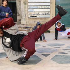 Man makes a breakdance move in front of three onlookers.