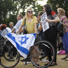 "A woman wearing a yellow top holds a bicycle with a blue and white flag draped over it, while talking to another woman holding a placard that reads ""Labour: For the Many, Not the Jew."""