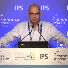 A bald man in a shirt stands at a conference podium speaking into a mic