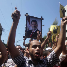 Large photo of Morsi carried above protesters