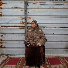 Woman sits in front of a wall, with a dark red rug beneath her feet.