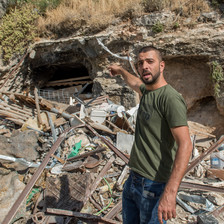 A man points to some rubble behind him