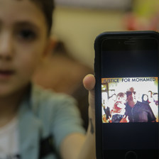 A boy holds a mobile phone with a picture of a man holding a baby