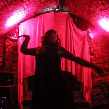 A dark silhouette against a red curtain of a person dancing