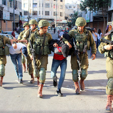 Armed soldiers detain two handcuffed men