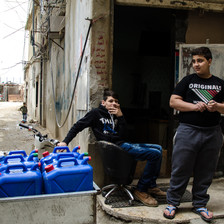 Two boys are next to several large blue plastic water canisters.