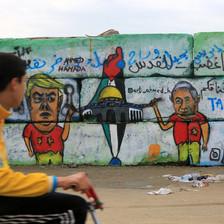 A boy looks at graffiti on a wall