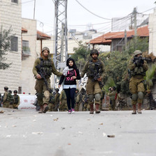 Two armed soldiers walk with a young girl between them while a third points a rifle somewhere in the distance
