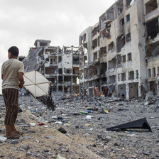 Boy holds kite in front of bombed-out multi-story buildings