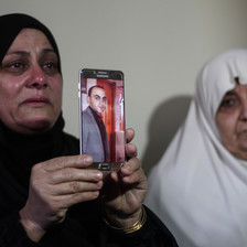 Two women cry, one holds up a picture of a man displayed on a phone