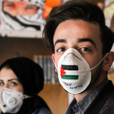 A man and a woman wear painted face masks one bearing the Palestinian flag and  words stay at home