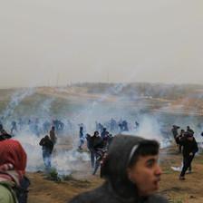 People in a field run amid streaks of smoke