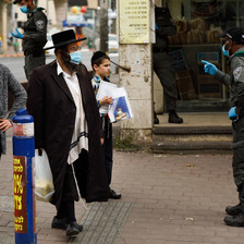 Israeli policeman in face mask gestures at two men in masks and a boy