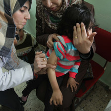 A nurse injects a young child whose face is diverted by her mother