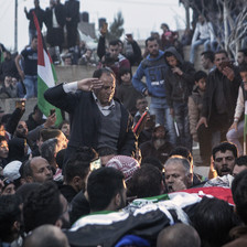 Man salutes corpse carried by mourners
