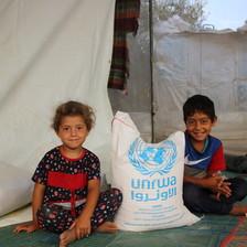 Two children sit on the ground