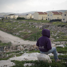 Youth sits with back turned to camera in front of Israeli settlement