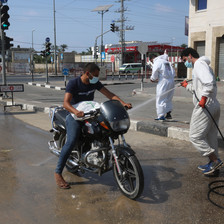 Man wearing white hoses down a motorcycle