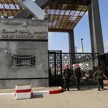 Three men in uniform stand beside a locked gate