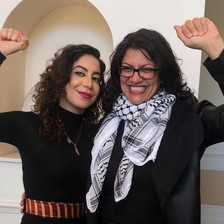 Two women embrace and raise fists