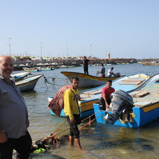 Three men stand near fishing vessels
