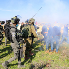 Uniformed soldiers face off against unarmed protestors hidden by a cloud of tear gas