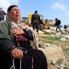 Woman sits on a rock with her hand on her chest as bulldozer operates in the background