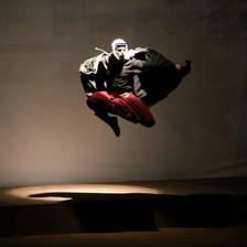 A man in traditional Palestinian black and white headgear flies through the air