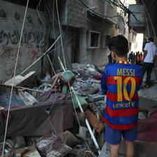 Child stands amid debris left after a bomb attack