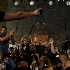 Men carried on shoulders in crowd make victory signs with their hands in front of Old City wall