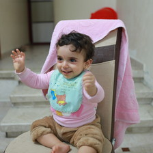 A young child sits on a chair and smiles
