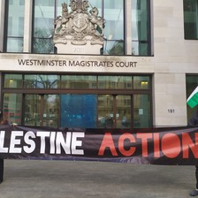 """Two protesters hold a """"Palestine Action"""" banner outside a court"""