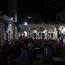 Men pray in the dark in an outdoor mosque courtyard