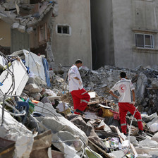 Two health workers stand in the rubble of a destroyed building
