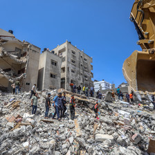 People walk over rubble of destroyed buildings