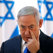 Benjamin Netanyahu touches a finger to his face
