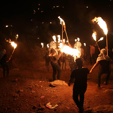 A group of men with lit torches walk across a field in the night